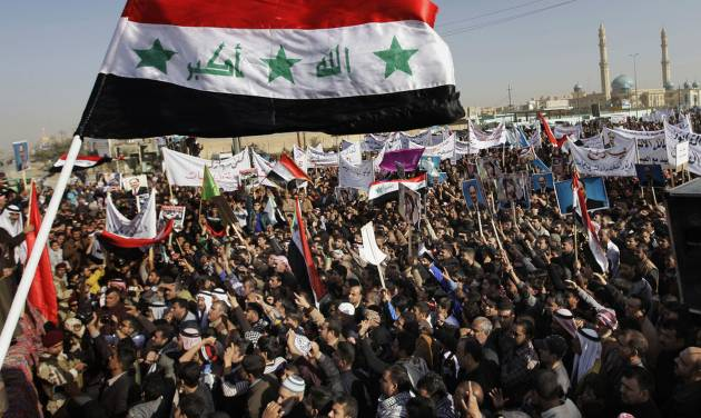 Protesters chant slogans against the Iraq's Shiite-led government as they wave national flags and hold posters of Sunni Finance Minister Rafia al-Issawi during a demonstration in Fallujah, 40 miles (65 kilometers) west of Baghdad, Iraq, Sunday, Dec. 23, 2012. Thousands of protesters have demonstrated in Iraq's western Sunni heartland following the arrest of bodyguards assigned to the finance minister, who draws support from the area. The Khulafa al-Rashideen mosque is seen at right. (AP Photo/ Khalid Mohammed)