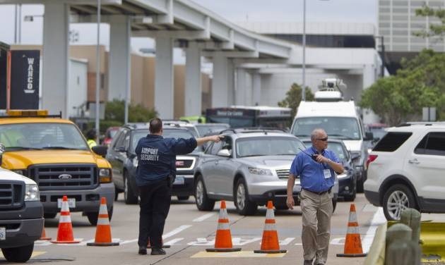 Airport security members divert traffic around the Marriott before getting to Terminal B at Bush Intercontinental Airport on Thursday, May 2, 2013 in Houston.   Shots were fired near a ticket counter, critically injuring one armed man and sending people in the terminal scrambling and screaming, a Houston police spokesman and witnesses said.   One person has been taken to an area hospital with life threatening injuries. It was not immediately clear who fired the shots.  (AP Photo/Houston Chronicle, Karen Warren ) MANDATORY CREDIT