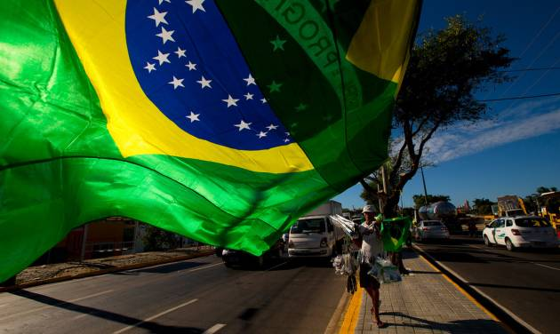 A street vendor sells representations of Brazil's national flags near the Arena Castelao  in  Fortaleza, Brazil, Wednesday, June 11, 2014.  The Brazil 2014 Word Cup soccer tournament is set to begin Thursday. (AP Photo/Fernando Llano)