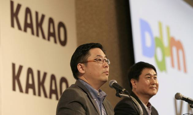 Daum Communications Corp. CEO Choi Sae-hoon, left, and Kakao Corp. CEO Sirgoo Lee listen to reporter's question during a press conference in Seoul, South Korea, Monday, May 26, 2014. Mobile messenger service Kakao Talk is seeking a backdoor listing on the South Korean stock exchange by combining with the country's second largest Internet portal. Daum Communications Corp. and Kakao Corp. said Monday that Kakao shareholders will get 1.556 Daum shares for each Kakao share they own. (AP Photo/Lee Jin-man)