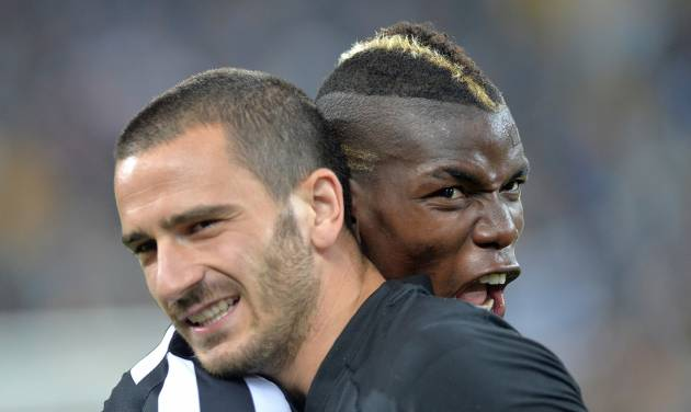 Juventus players Paul Pogba, right, and Leonardo Bonucci, left, celebrate at the end of a Serie A soccer match againsts Atalanta, at the Juventus stadium, in Turin, Italy, Monday, May 6, 2014. Juventus clinched its third straight and 30th overall Serie A title. (AP Photo/Massimo Pinca)