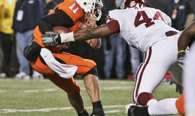 Oklahoma defensive end Jeremy Beal, right, tackled Oklahoma State quarterback Zac Robinson, left, and forces a fumble in the third quarter of an NCAA college football game in Stillwater, Okla., Saturday, Nov. 29, 2008. (AP Photo/Sue Ogrocki)