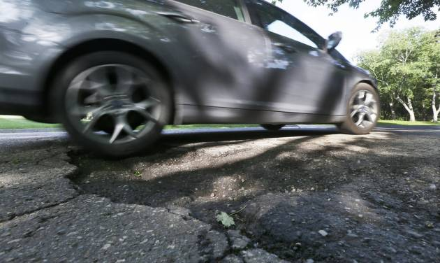 An automobile drives through a pothole in Bloomfield Township, Mich., Thursday, June 12, 2014. An effort to more than double Michigan's gasoline tax was defeated in the Republican-led state Senate, which left lawmakers scrambling to pass a scaled-back plan to improve deteriorating roads on their last day before adjourning for much of the summer. (AP Photo/Carlos Osorio)