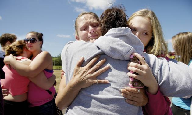 Brandi Wilson, left, and her daughter, Trisha Wilson, 15, right, embrace Trish Hall, a mother waiting for her student, as students arrived at the Fred Meyer grocery store parking lot in Wood Village, Ore., after a shooting at Reynolds High School Tuesday, June 10, 2014, in nearby Troutdale. A gunman killed a student at the high school east of Portland Tuesday and the shooter is also dead, police said. (AP Photo/Troy Wayrynen)