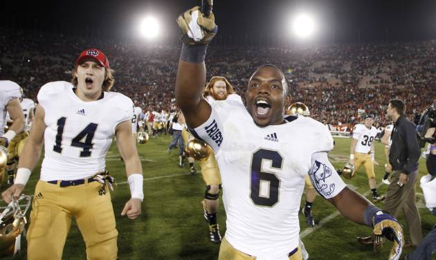 Notre Dame running back Theo Riddick, right, and wide receiver Luke Massa, left, celebrate after Notre Dame defeated Southern California 22-13 in an NCAA college football game, Saturday, Nov. 24, 2012, in Los Angeles. (AP Photo/Danny Moloshok)