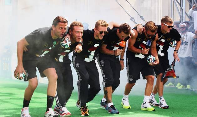 """German soccer players from left: Roman Weidenfeller, Shkodran Mustafi, Andre Schuerrle, Miroslav Klose, Mario Goetze and Toni Kroos celebrate on stage at the German team victory ceremony , near the Brandenburg Gate in Berlin,  Tuesday July 15,  2014.  Germany's World Cup winners shared their fourth title with hundreds of thousands of fans by parading the trophy through cheering throngs to celebrate at the Brandenburg Gate on Tuesday. An estimated 400,000 people packed the """"fan mile"""" in front of the Berlin landmark to welcome home coach Joachim Loew's team and the trophy — which returned to Germany for the first time in 24 years. (AP Photo/ Alex Grimm,Pool)"""