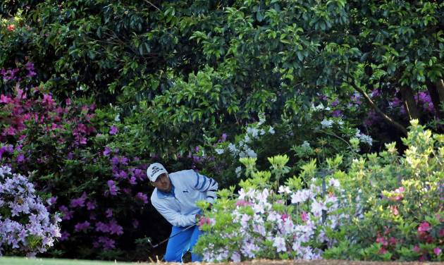 Jonas Blixt, of Sweden, looks out from behind the bushes off the second fairway after hitting out of the rough during the first round of the Masters golf tournament Thursday, April 10, 2014, in Augusta, Ga. (AP Photo/Matt Slocum)