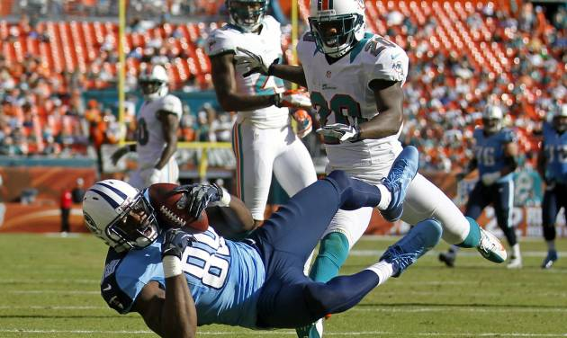 Tennessee Titans tight end Jared Cook, bottom, scores a touchdown on a 26-yard pass in front of Miami Dolphins free safety Reshad Jones (20) during the second half of an NFL football game on Sunday, Nov. 11, 2012, in Miami. (AP Photo/John Bazemore)