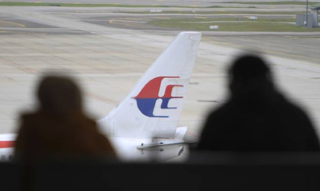 Visitors look out from viewing gallery as a Malaysia Airlines jet sits in the tarmac at the Kuala Lumpur International Airport (KLIA) in Sepang, Malaysia, Friday, Aug. 29, 2014. Malaysia Airlines will cut 6,000 workers as part of an overhaul announced Friday to revive its damaged brand after being hit by double passenger jet disasters. (AP Photo/Lai Seng Sin)