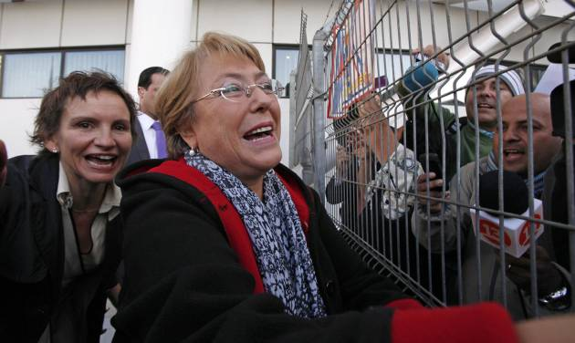 Chile's former president Michelle Bachelet greets supporters and journalists upon her arrival at the Arturo Merino Benitez Internationl Airport in Santiago, Chile, Wednesday, March 27, 2013. Bachelet has returned to the South American country after ending a two-year stint heading the U.N. women's agency in New York. She landed in the capital Wednesday amid wide speculation she'll run for president again this year. Pictured behind Bachelet is Santiago Mayor Carolina Toha. (AP Photo/Luis Hidalgo)