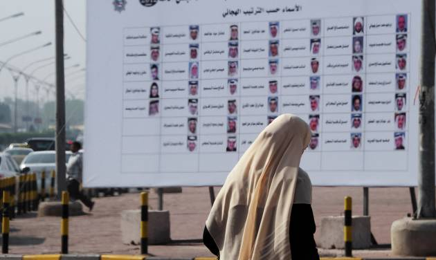 A Kuwaiti woman walks past a board with the names and photos of next December's election candidates in Salwa, Kuwait, Sunday, Nov. 25, 2012. There is little middle ground but plenty of high-stakes tension as Kuwait stumbles toward elections for the most politically empowered parliament among the Gulf Arab states. (AP Photo/Gustavo Ferrari)