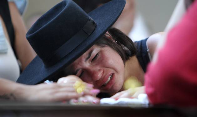 ADDS FACT THAT THE WOMAN WAS GIRLFRIEND OF THE VICTIM.- A woman cries over the coffin of  her boyfriend at a gymnasium where bodies were brought for identification in Santa Maria city, Rio Grande do Sul state, Brazil, Sunday, Jan. 27, 2013. They were both at the Kiss nightclub when flames raced through the crowded club in southern Brazil early Sunday, killing more than 230 people as panicked partygoers gasped for breath in the smoke-filled air, stampeding toward a single exit partially blocked by those already dead. (AP Photo/Nabor Goulart)