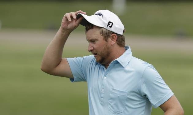 Brice Garnett take off his cap after sinking his putt on the 18the hole during the second round of the PGA Colonial golf tournament in Fort Worth, Texas, Friday, May 23, 2014. (AP Photo/LM Otero)