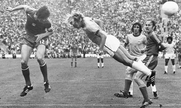 FILE - In this July 6, 1974 file photo, Deyna of Poland, left, heads the ball, while Brazil's Marinho challenges. Poland's Grzegorz Lato looks on, at right, during third place play-off in Munich, West Germany. On this day: Poland beats Brazil 1-0 to claim third place in the 1974 World Cup with Lato scoring the only goal, taking his tournament tally to 7. (AP Photo/File)
