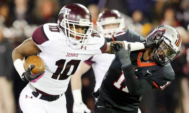 Jenks' Steven Parker pushes off Union's Robert Thomas on a gain during Thursday night's 6A title game.  Photo by MICHAEL WYKE, Tulsa World
