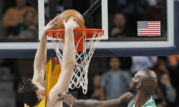 Denver Nuggets forward Danilo Gallinari, of Italy, drops the ball in for a basket as Boston Celtics forward Kevin Garnet, right, and guard Avery Bradley watch during the first quarter of an NBA basketball game in Denver on Tuesday, Feb. 19, 2013. (AP Photo/David Zalubowski)