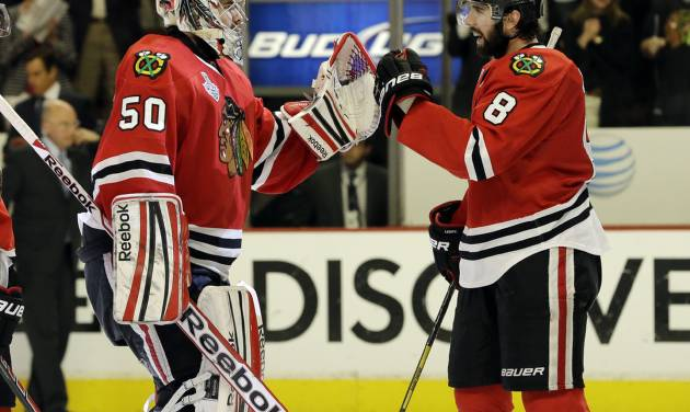 Chicago Blackhawks goalie Corey Crawford (50) celebrates with defenseman Nick Leddy (8) during the third overtime period of Game 1 in their NHL Stanley Cup Final hockey series, Thursday, June 13, 2013, in Chicago. (AP Photo/Nam Y. Huh)