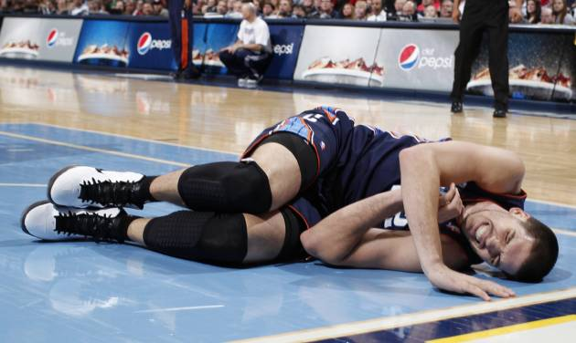 Charlotte Bobcats center Byron Mullens reacts injuring his leg while contesting a shot against the Denver Nuggets late in the fourth quarter of the Nuggets' 110-88 victory in an NBA basketball game in Denver, Saturday, Dec. 22, 2012. Mullens was helped off the court by teammates. (AP Photo/David Zalubowski)