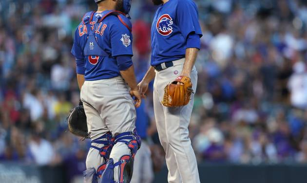 Chicago Cubs catcher Wellington Castillo, left, confers with starting pitcher Jake Arrieta after Arrieta gave up an RBI single to Colorado Rockies' Michael McKenry in the fourth inning of the Rockies' 13-4 victory in a baseball game in Denver on Wednesday, Aug. 6, 2014. (AP Photo/David Zalubowski)
