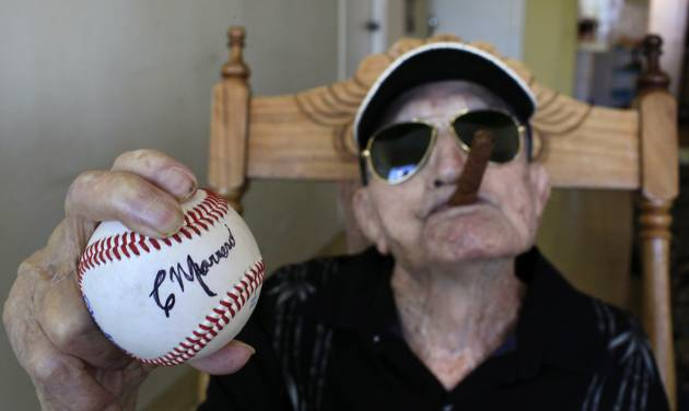 In this April 23, 2013 photo, Cuba's former pitcher Conrado Marrero, the world's oldest living former major league baseball player, holds up a baseball with his signature at his home, two days before is 102nd birthday, as he holds an unlit cigar in his mouth in Havana, Cuba. In addition to his longevity, the former Washington Senator has much to celebrate this year. After a long wait, he finally received a $20,000 payout from Major League baseball granted to old-timers who played between 1947 and 1979. The money had been held up since 2011 due to issues surrounding the 51-year-old U.S. embargo on Cuba, which prohibits most bank transfers to the Communist-run island. But the payout finally arrived in two parts, one at the end of last year, and the second a few months ago, according to Marrero's family. (AP Photo/Franklin Reyes)