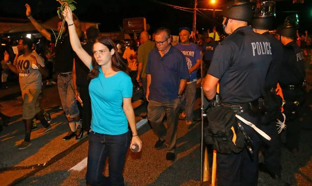 A protester holds roses in the air as she marches with others past police officers in Ferguson, Mo. on Tuesday, Aug. 19, 2014. On Saturday, Aug. 9, 2014, a white police officer fatally shot Michael Brown, an unarmed black teenager, in the St. Louis suburb. (AP Photo/Atlanta Journal-Constitution, Curtis Compton)