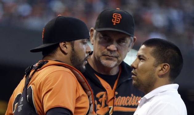 FILE - In this July 25, 2014, file photo, San Francisco Giants manager Bruce Bochy, center, and a trainer, right, check on the condition of Giants catcher Hector Sanchez, left, in the second inning of a baseball game against the Los Angeles Dodgers in San Francisco. Sanchez is expected to miss the remainder of the season while recovering from a second concussion this year. Sanchez returned Wednesday, Aug. 27, 2014, to AT&T Park after an examination by concussion specialist Dr. Micky Collins at the University of Pittsburgh and was instructed to rest for three weeks. (AP Photo/File)