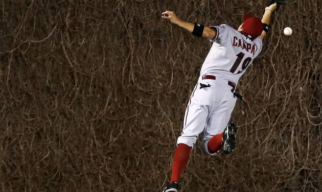 Arizona Diamondbacks center fielder Tony Campana misses the catch on an RBI double hit by the Chicago Cubs' Travis Wood during the fourth inning of a baseball game on Monday, April 21, 2014, in Chicago. (AP Photo/Andrew A. Nelles)