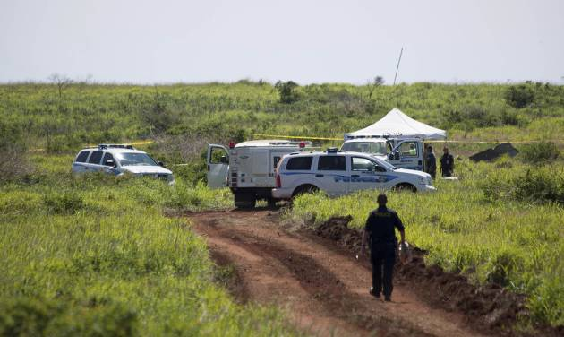 This Thursday, Feb. 27, 2014 photo released by Russell deJetley shows officials at the site of a plane crash in Lanai City, Hawaii. A small plane crashed and burst into flames shortly after takeoff from Hawaii's Lanai island, killing three people and leaving three others injured, authorities said Thursday. The crash occurred around 9:30 p.m. Wednesday about a mile from Lanai Airport in the Miki Basin area, Maui County spokesman Rod Antone told The Associated Press. (AP Photo/Russell deJetley)