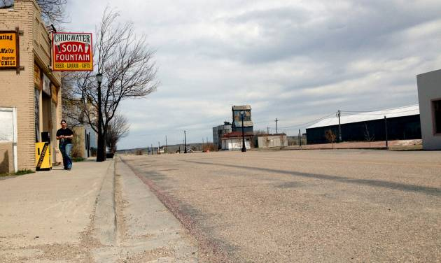 This April 29,2013 photo shows an unidentified woman strolls down an otherwise empty street in Chugwater, Wyo. The 200 or so residents of Chugwater have had nowhere to get gas since a sport utility vehicle crashed into and burned down the Horton's Corner convenience store on Dec. 30,2012, which was the town's only gas station. Since then, people have had to drive at least 48 miles round-trip to fill up in a neighboring town. (AP Photo/Mead Gruver)