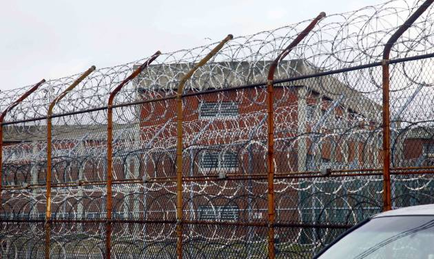 FILE - In this March 16, 2011 file photo, inmate housing on New York's Rikers Island correctional facility can be seen on the other side of a fence topped with razor wire. The Independent Budget Office found it cost $167,731 in 2012 to house 12,287 daily New York City inmates, which is about $460-per-inmate-per-day. (AP Photo/Bebeto Matthews, File)