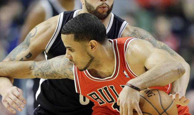 Brooklyn Nets guard Deron Williams, behind, tries to steal the ball from Chicago Bulls guard D.J. Augustin during the first half of an NBA basketball game in Chicago on Thursday, Feb. 13, 2014. (AP Photo/Nam Y. Huh)