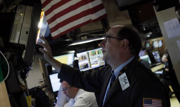 In this Monday, June 10, 2013 photo, trader Edward Landi check a screen in a booth on the floor of the New York Stock Exchange. Global stock markets traded fitfully Tuesday June 18, 2013 as investors watched for signs of a possible change in U.S. stimulus efforts by the Federal Reserve. (AP Photo/Richard Drew)