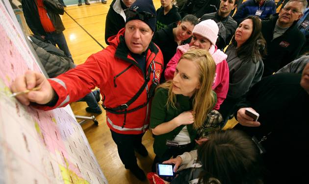 Unified firefighter Chris Thurman points out a meeting point to Christi Green and other volunteers before they leave to help search for 13-year-old Brooklyn Gittins a  in Herriman, Utah, on Thursday, Jan. 10, 2013.  Several hundred volunteers dressed for the cold showed up at a Mormon meetinghouse Thursday to help search for a 13-year-old Utah girl who went missing without her shoes, coat or cellphone. (AP Photo/Kristin Murphy, Deseret News) NO SALES; MAGS OUT; SALT LAKE TRIBUNE OUT;  PROVO DAILY HERALD OUT