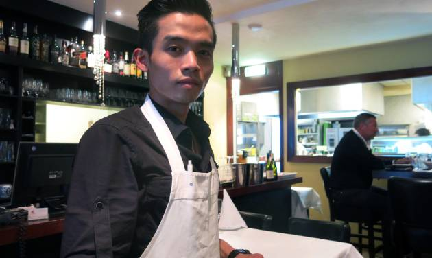 In this Aug. 12, 2014 photo, Kevin Fan poses for a photo at Asian Glories restaurant in Rotterdam, Netherlands. Fan is grappling with the job of running two Rotterdam restaurants that were owned by his parents, who, along with his grandmother, were on the Malaysia Airlines plane shot down over Ukraine. Fan's father, who went by Popo, was the chef at Asian Glories; his mother Jenny was the hostess. (AP Photo/Toby Sterling)