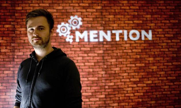 """In this Sunday, June 1, 2014 photo, Nils Pihl stands in front of his company logo on the wall at his apartment, which he converted to an office in Beijing, China. Pihl has spent 18 months building what he calls cutting-edge software to crunch """"really big data sets."""" But instead of going to Silicon Valley, the 27-year-old Swede and his four colleagues have been working on his invention from a small apartment overlooking smoggy northwest Beijing. (AP Photo/Andy Wong)"""