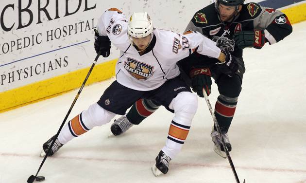 OKC's Teemu Hartikainen (10) skates against Houston's Drew Bagnall (4) during a game between the Oklahoma City Barons and the Houston Aeros at the Cox Convention Center in Oklahoma City, Sunday, April 22, 2012.  Photo by Garett Fisbeck, For The Oklahoman
