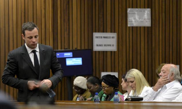 Oscar Pistorius, left, walks past Barry Steenkamp, the father of Reeva Steenkamp, right, during his trial, in Pretoria, South Africa, Friday, Aug. 8, 2014. The chief defense lawyer for Pistorius delivered final arguments in the athlete's   trial on Friday, alleging that Pistorius thought he was in danger when he killed girlfriend Reeva Steenkamp and also that police mishandled evidence at the house where the shooting happened. (AP Photo/ Herman Verwey, Pool)