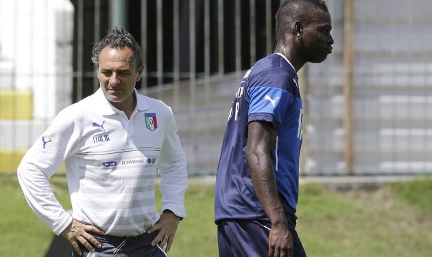 Italy coach Cesare Prandelli stands on the pitch as forward Mario Balotelli walks past during a training session at the Maria Lamas Farache stadium in Natal, Brazil, Sunday, June 22, 2014. Italy plays in group D of the Brazil 2014 soccer World Cup. (AP Photo/Antonio Calanni)