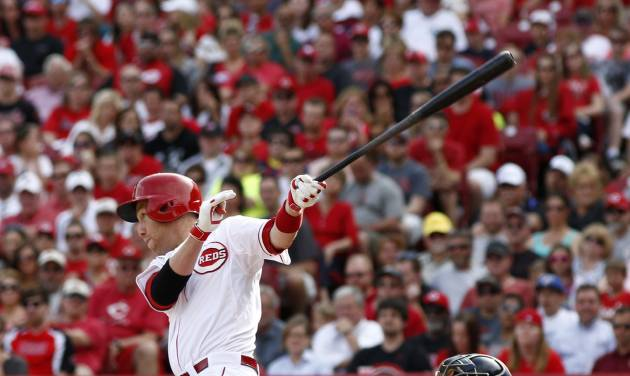 Cincinnati Reds' Todd Frazier, left, hits a sacrifice fly off Milwaukee Brewers starting pitcher Kyle Lohse scoring Brandon Phillips during the fourth inning of a baseball game, Sunday, May 4, 2014, in Cincinnati. Brewers catcher Jonathan Lucroy watches at right.  (AP Photo/David Kohl)