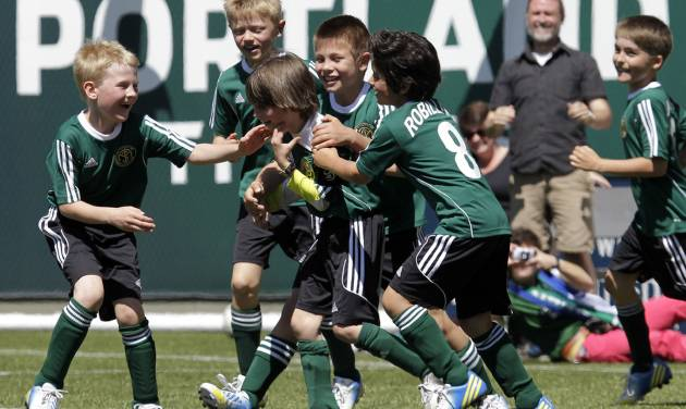 Atticus Lane-Dupre, 8, third from left, is congratulated by his teammates on the Green Machine soccer team after scoring the winning goal against the MLS Portland Timbers soccer team in Portland, Ore., Wednesday, May 1, 2013.  The Timbers and Make-A-Wish Oregon treated Atticus' team to a game at Jeld-Wen Field with more than 3,000 fans coming out to lend their support. Atticus missed the Green Machine's final match last fall because of cancer treatment.  (AP Photo/Don Ryan)