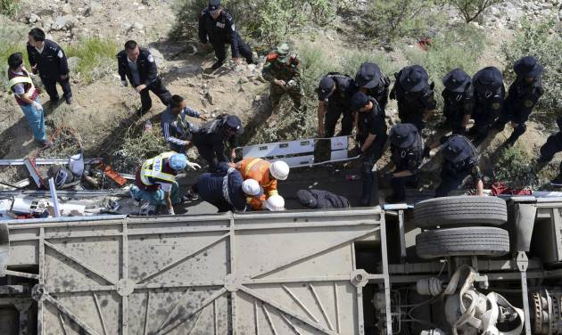 In this photo released by China's Xinhua News Agency, rescuers try to pull out bodies and survivors from an overturned tour bus after it fell off a 10-meter (30-foot) cliff in Nyemo County, southwest China's mountainous region of Tibet Saturday, Aug. 9, 2014. Xinhua reported the bus carrying about 40 people careened after it crashed in a pileup involving a sports utility vehicle and a pickup truck on a state road. Casualty details were not immediately known. (AP Photo/Xinhua, Chogo) NO SALES