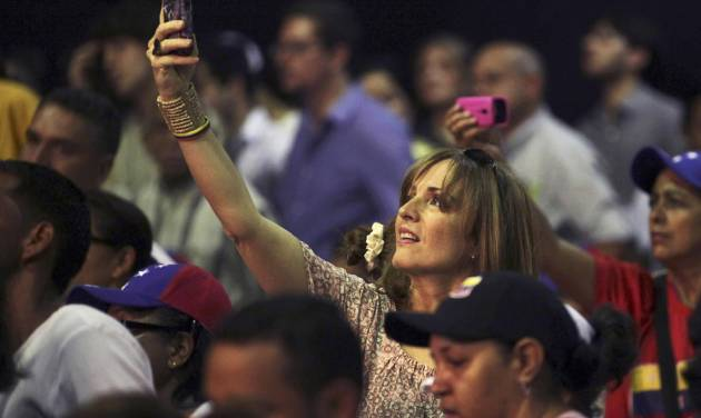 FILE - In this Sept. 10, 2012 file photo, supporters of opposition presidential candidate Henrique Capriles take photos with their smart phones as he campaigns in Caracas, Venezuela. The battle for Venezuela is being fought as much online as in the streets, with opposition activists flooding social media with video of security force aggression, Internet service reported cut to most of a conflict-rattled western state and the government blocking select websites. (AP Photo/Fernando Llano, File)