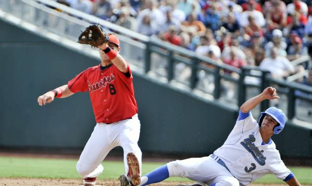 UCLA's Kevin Kramer (3) beats the throw to second baseman Maxx Tissenbaum (8), on a fielder's choice by Kevin Williams, in the first inning of an NCAA College World Series baseball game in Omaha, Neb., Friday, June 15, 2012. (AP Photo/Eric Francis)