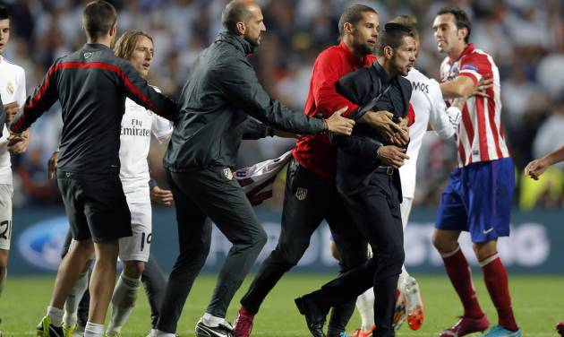 Atletico's coach Diego Simeone, centre right,  is held back by his staff, during the Champions League final soccer match between Atletico de Madrid and Real Madrid in Lisbon, Portugal, Saturday, May 24, 2014. (AP Photo/Daniel Ochoa de Olza)