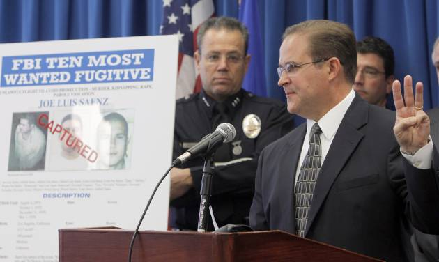 Bill Lewis, the FBI Los Angeles Assistant Director in Charge, right, and Los Angeles Police Assistant Chief Michael Moore, left, announce the arrest of suspect Joe Luis Saenz, one of the FBI Ten Most Wanted fugitives after he was arrested Thursday, Nov. 22, 2012, in a joint operation with the Mexican government, during a news conference in Los Angeles Monday Nov. 26 , 2012. (AP Photo/Nick Ut)