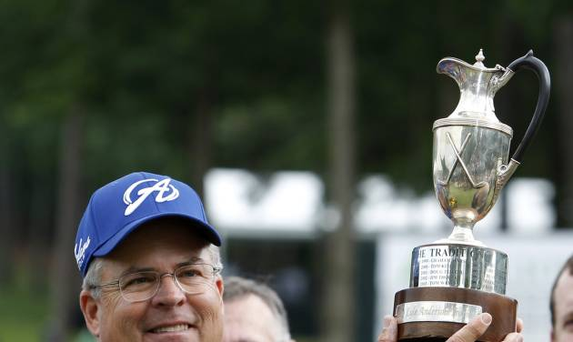 Kenny Perry holds up the trophy after winning the Champions Tour Regions Tradition golf tournament on Sunday, May 18, 2014, in Birmingham, Ala. (AP Photo/Butch Dill)