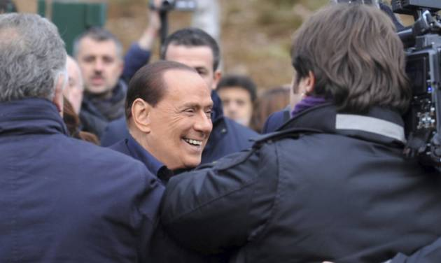 """In this photo provided by AC Milan press office, billionaire media baron Silvio Berlusconi is surrounded by media as announces he is running for a fourth term as premier,  during a visit to the AC Milan Milanello soccer training center, near Milan, Italy, Saturday, Dec. 8, 2012. """"I'm running to win,"""" Berlusconi told reporters outside the training facilities of his soccer team AC Milan. Berlusconi resigned in disgrace a year ago and it seems he is poised to re-enter politics.  (AP Photo/Gianni Buzzi, AC Milan press office)"""