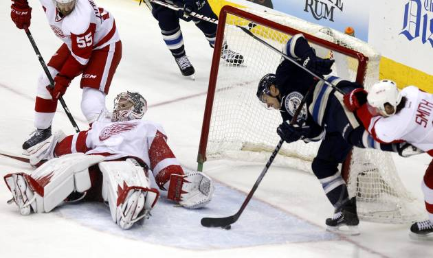 Columbus Blue Jackets' Cam Atkinson (13) scores a goal against Detroit Red Wings goalie Jimmy Howard (35), Niklas Kronwall (55), of Sweden, and Brendan Smith (2) in the third period of an NHL hockey game in Columbus, Ohio, Tuesday, March 25, 2014. Columbus won 4-2. (AP Photo/Paul Vernon)