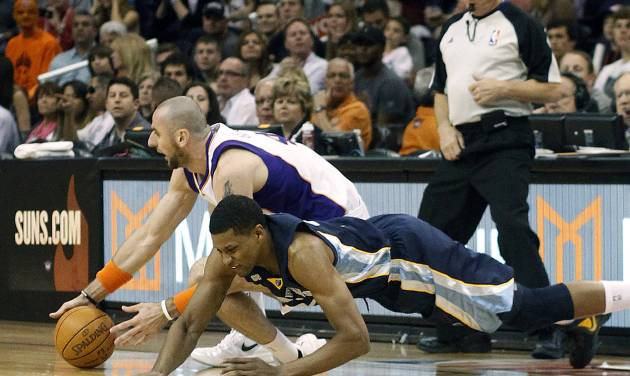 Phoenix Suns center Marcin Gortat, left, of Poland, and Memphis Grizzlies forward Rudy Gay, right, struggle to gain control of a loose ball in the first quarter of an NBA basketball game Saturday, March 10, 20112, in Phoenix.(AP Photo/Paul Connors)