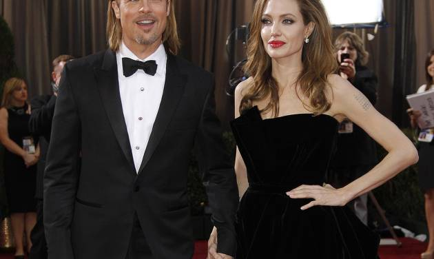 """FILE - This Feb. 26, 2012 file photo shows actress Angelina Jolie, right, and actor Brad Pitt at the 84th Academy Awards in the Hollywood section of Los Angeles. Jolie says that she has had a preventive double mastectomy after learning she carried a gene that made it extremely likely she would get breast cancer. The Oscar-winning actress and partner to Brad Pitt made the announcement in  an op-ed she authored for Tuesday's New York Times under the headline, """"My Medical Choice."""" She writes that between early February and late April she completed three months of surgical procedures to remove both breasts. (AP Photo/Amy Sancetta, file)"""